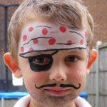 menino loiro com a cara pintada de pirata. Na testa, tinta branca com bolinhas pretas imitando a bandana. A tinta preta foi usada também para fazer uma tapa-olho e o bigodinho fininho e curvado para cima.
