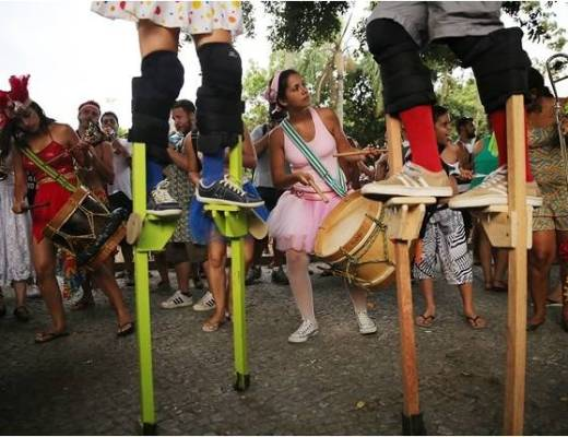 Bloco de rua, pessoas fantasiadas de bailarina sobre pernas de pau. alguns tocam tambores rústicos