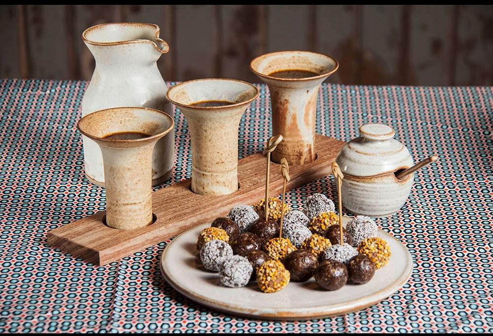 mesa com toalha branca com detalhes redondos em cor azul e vermelho. Ao centro uma base de madeira, com tres taças em cerâmicas, altas com chocolate, ao lado um pote de açucar e junto a ele um prato de cerâmica com diversos doces brigadeiro.