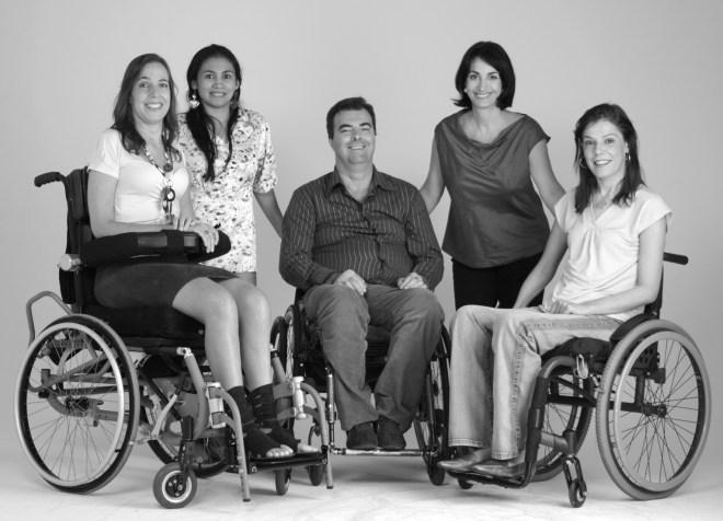 Claudia Matarazzo, de pé com as mãos apoiadas , Está entre a deputada Mara Gabriili e Flavia Cintra, ambas cadeirantes, imagem do livro Vai Encarar.