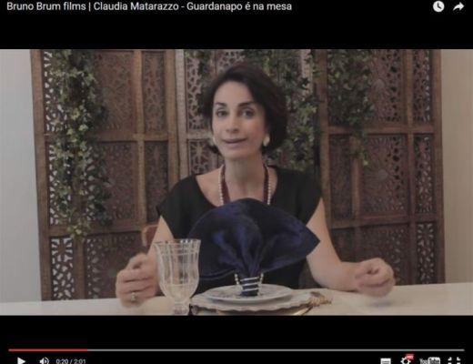 Claudia Matarazzo sentada numa mesa de jantar , diante de um copo com guardanapos escuros a sua frente, ela veste uma blusa cor preta. ao fundo um biombo em madeira.