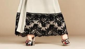 por baixo de uma túnica creme com renda preta aparecem os pés da modelo calçando sapatos de saltos altos com flores multicoloridas trabalhadas e aplicadas no corpo do calçado em diferentes texturas.