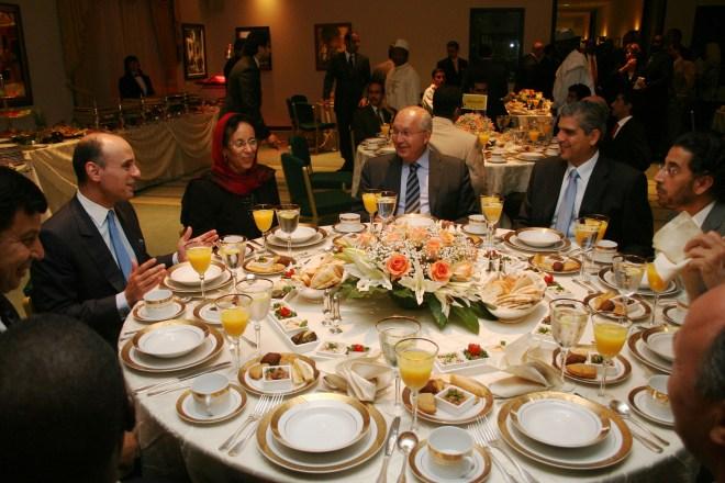 mesa de jantar redonda com 9 lugares, completa com porcelanas brancas com bordas douradas, taças de vinhos e um vaso de flores ao centro. Temos oito diplomatas usando ternos cor escura e uma mulher usando um véu, cor vermelha, sobre a cabeça,