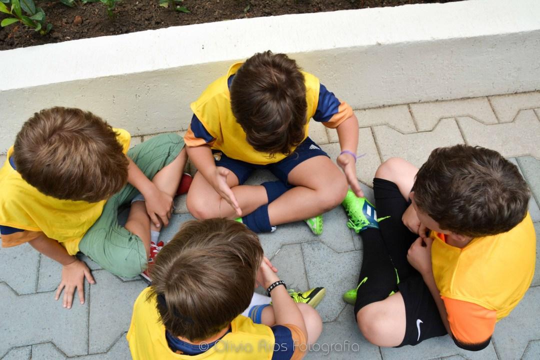 4 crianças sentadas no chão, usando camisetas cor amarela. eles usam chuteiras e diversas cores de shorts. Eles conversam entre si.