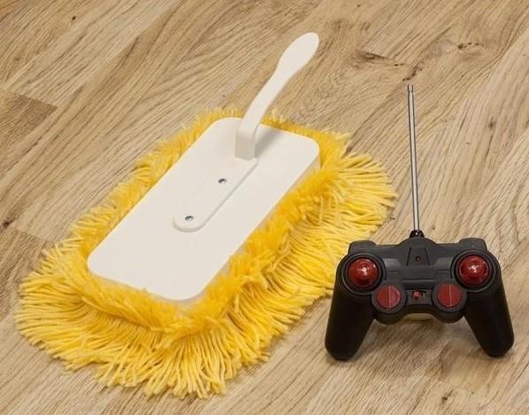 vassoura manual em escovas amarelas sobre um assoalho de madeira, ao lado um controle remoto .