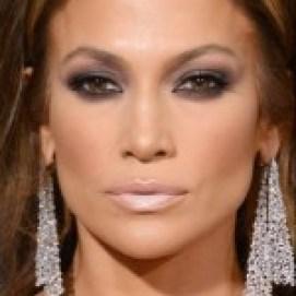 atriz Jennifer Lopez, durante uma entrega de prêmio. Ela usa cabelos lisos e soltos, brincos estilo pingente, e um vestido longo, com decote acentuado e ousado.