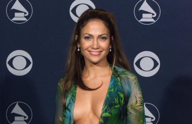 Atriz Jennifer Lopez, durante uma entrega de Prêmios. Está de pé em imagem frontal, Usa um vestido tipo capa, transparente, em tons verdes, com um decote ousado até a região umbigo. Ela sorri.