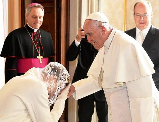 Princesa Charlene de Mônaco, faz reverência usando casaco longo na cor branca e sua cabeça coberta por um véu rendado, faz reverência e beija o anel do pescador, símbolo do papa. do Papa Francisco. Ao fundo o Principe Albert de Mônaco sorri.