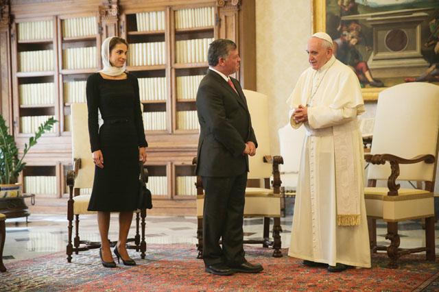 No salão de audiência do Vaticano, está de pé o Papa Francisco recebe o Rei Abdullah vestindo terno escuro e Rainha Rânia da Jordânia usando vestido preto, e véu rendado na cor creme. Sua Santidade veste sua tunica branca