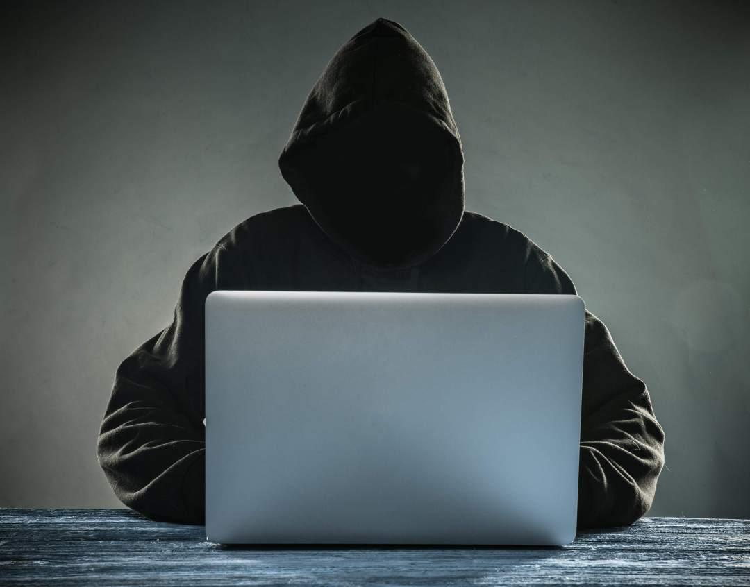 numa mesa um homem usando casaco e capuz , está a usando um notebook. Não se consegue ver seu rosto em função da sombra do capuz.
