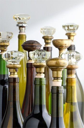 Várias garrafas de bebidas, de diversas cores, todas usando um rolha em cristal diferente. semelhante ao brilhante.