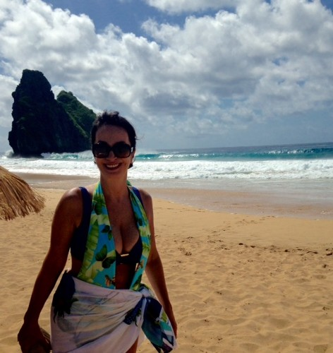 Claudia Matarazzo, numa das praias de Fernando de Noronha, usa cabelos presos , usa também uma saida de praia florida e um top azul. Usa óculos escuros grande e sorri.