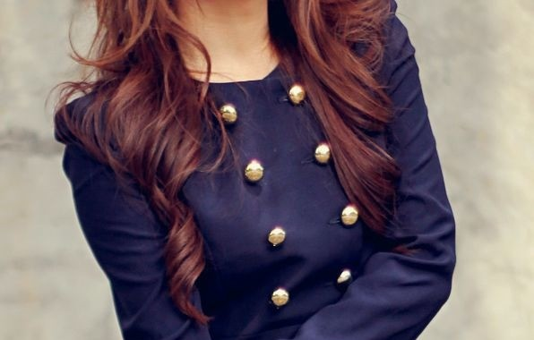 foto de uma moça onde não e vê o rosto e em close vemos seu lazer azul marinho com seis botões dourados se sobressaindo. O destaque é a cor com o dourado.