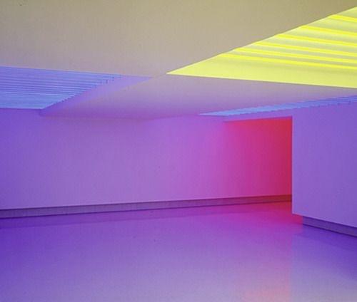 Uma foto de um espaço que tanto pode ser uma garagem quanto uma sala muito moderna. As paredes são totalmente brancas porém estão iluminadas com muita cor fazendo com que as frestas de espaço e sacas tenham efeitos de luz e sombra. Predominam os tons de rosa, lilás e amarelo. O espaço é grande e está vazio.