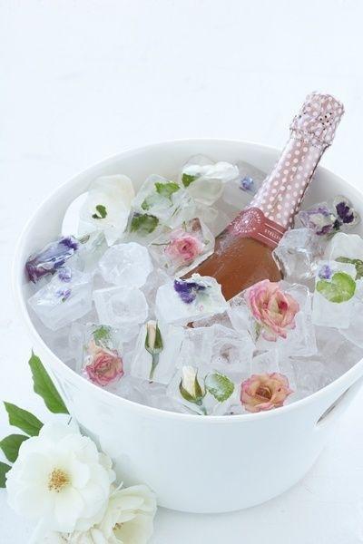 Em um balde de gelo branco que está em um fundo branco se vêem pedras de gelo com flores prensadas com uma garrafa de vinho rosé mergulhada até a metade com o gargalo a vista.