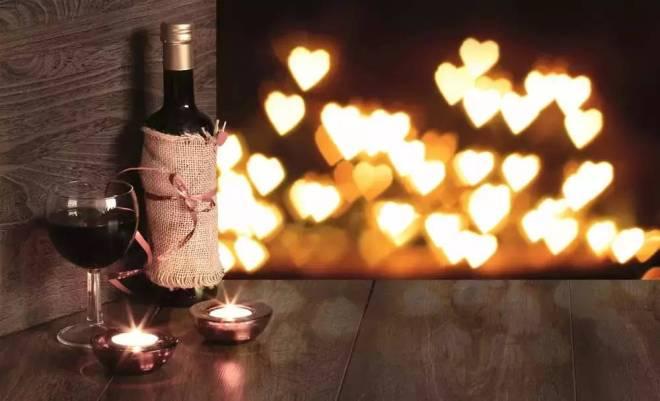 Sobre uma mesa de madeira está uma garrafa de vinho envolta em uma capa de juta rústica com das velas bem baixinhas a sua frente e taças. Ao fundo luzes em forma de coração iluminam o ambiente.