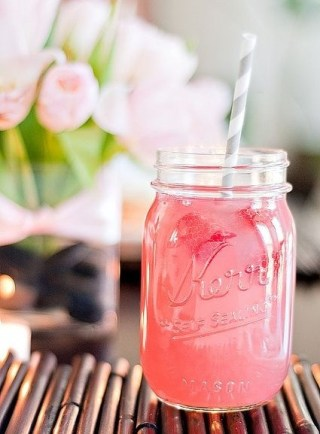 Em um pote de geléia está um suco cor de melancia : vermelho claro com um canudo listrado de cinza e branco. Ao fundo está um vaso de rosas cor de rosa desfocado.