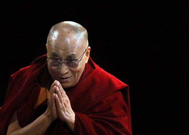 Venerável Dalai Lama, líder religioso do Tibet, num ambiente escuro, usa as túnicas marsala, símbolos dos monges tibetanos, as mãos unidas em mantra de oração. Ele tem o sorriso da compaixão. Ele é careca e usa óculos.