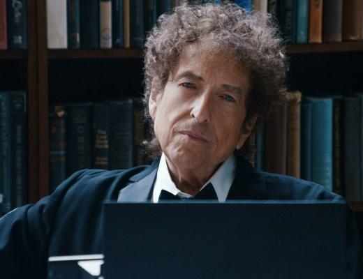 Cantor americano Bob Dylan em foto numa biblioteca , onde aparece seu rosto , cabelos desarrumados, rosto esguio, camisa branca e casaco preto. nariz afilado, olhos claros. Seu semblante é de contemplação de algo.