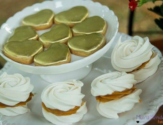 Foto em close de vários pequenos sanduíches de suspiros-merengues recheados de doce de leite estão colocados em volta de um prato que também tem outro merengues em formato de coração com a superfície dourada. O visual é festivo e apetitoso.
