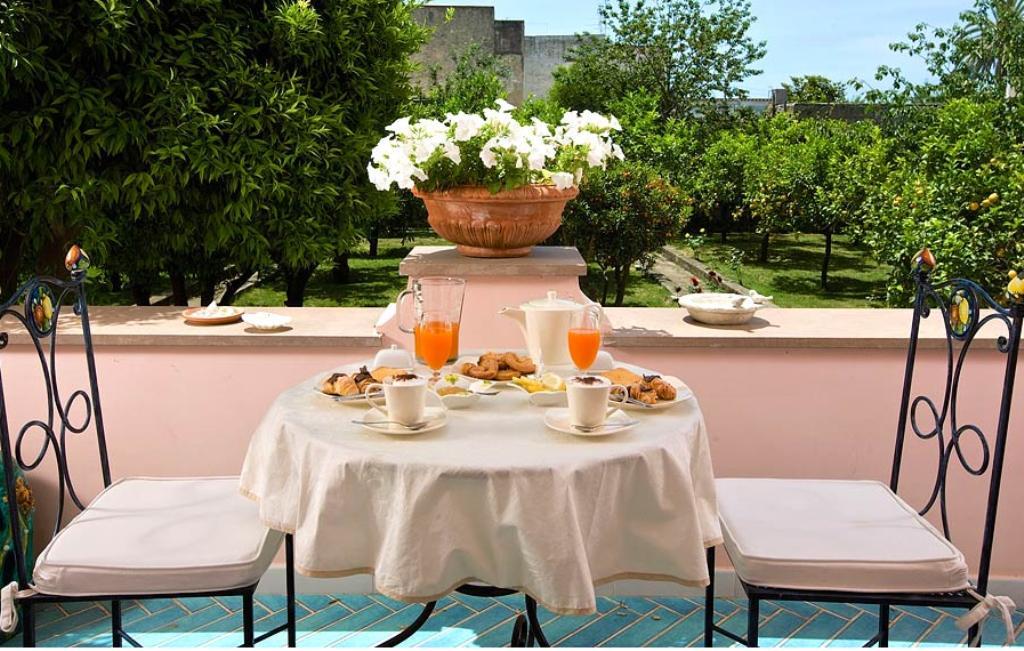 mesa de café da manhã, numa sacada de um hotel em Capri, Italia, num belíssimo cenário da italiano. Sobre a mesa com toalha com tecido claro, temos copos de sucos, xícaras , pães e ao fundo , flores num vazo .