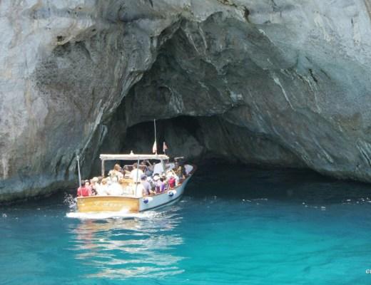 gruta de pedra no mar, com um barco com turistas, visitam esse ponto turístico de Capri, Italia. Um mar azul , águas límpidas e cor azul turquesa muito clara.
