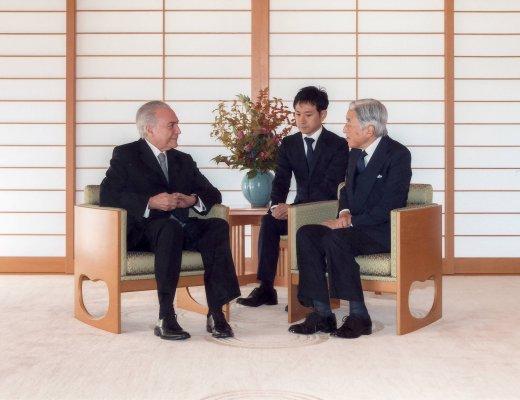 Sua Majestade Imperador Akihito do Japão recebe na Casa Imperial Japonesa o Presidente Michel Temer, do Brasil, estãn no Salão Imperial sentados o a ambos usam terno escuro , camisa branca e gravata escura. Estão conversando.