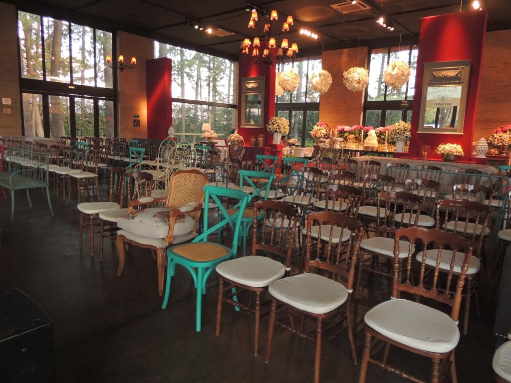 Várias fileiras de cadeiras de madeira estão colocadas em estilo auditório. Algumas são pintadas de branco, outras estão ao natural e ouras ainda coloridas. Todas com almofadas em tecido e harmoniosas entre si.