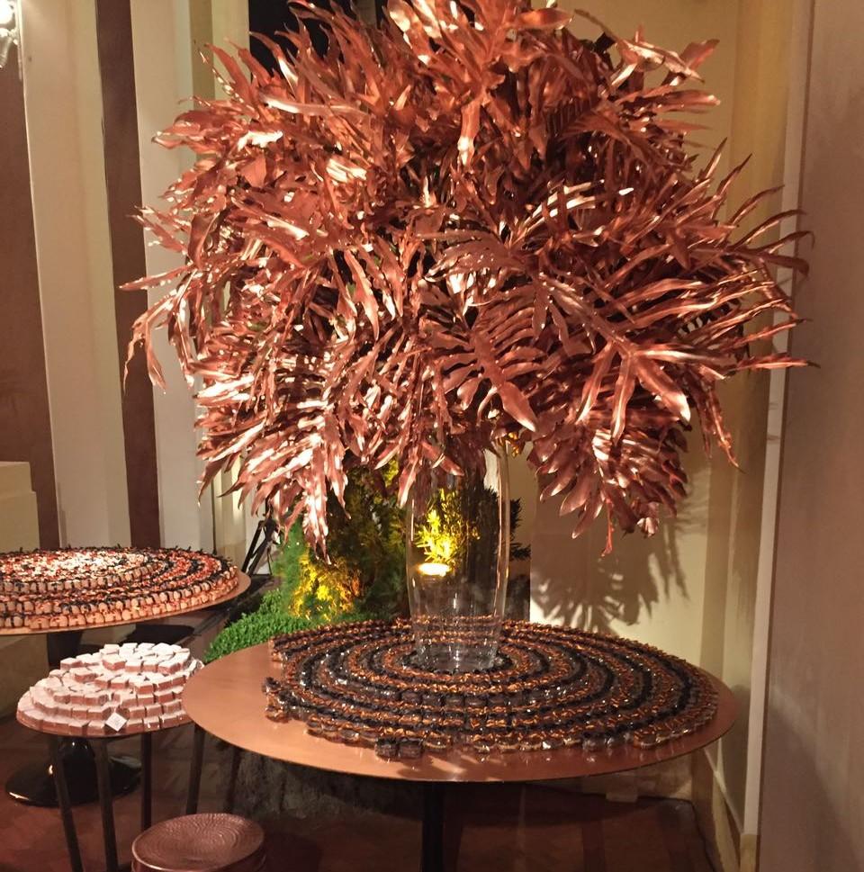 Um vaso grande de vidro com de folhagens tropicais pintadas de cor de bronze avermelhado está sobre uma mesa redonda de tampo igualmente cor de bronze. Ao redor da base do vaso estão dispostas fileiras de brigadeiros e docinhos dourados avermelhados intercaladas formando listras marrons e cor de bronze