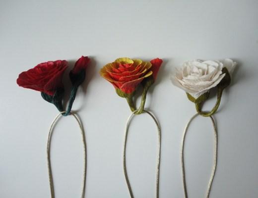 flores em papel crepom , coloridas, na imagem estão 3 flores , nas cores vermelha, amarelo-vermelha e branca. Tendo como suporte um barbante