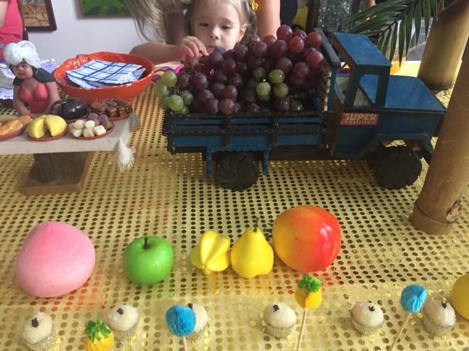 Mesa de festa, com mini caminhão, com uvas roxas e outras frutas fantasias decorando a mesa.