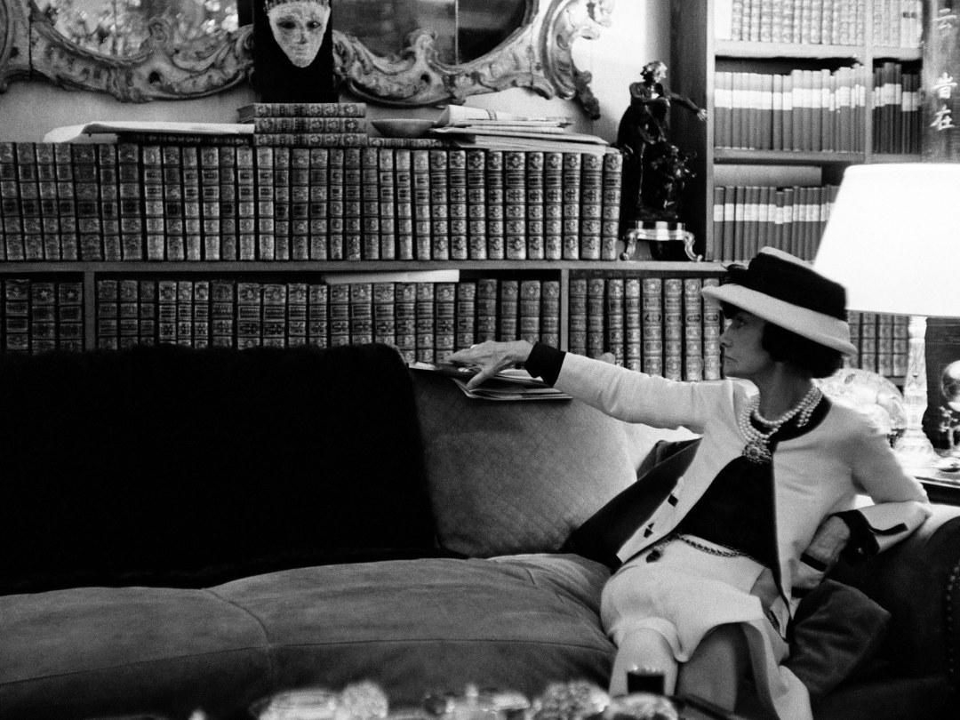 A estilista Coco Chanel - na sala de sua casa-atelier- sentada no sofá - Ela usa chapéu e um conjunto claro. Ao fundo uma prateleira com diversos livros