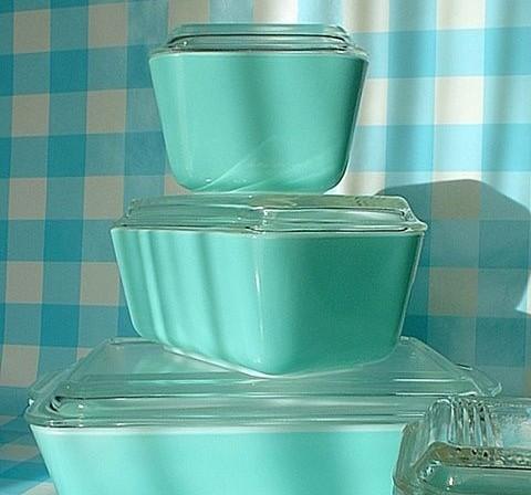 3 potes retangulares em vidro turquesa empilhados com a tampa de vidro transparente canelada.