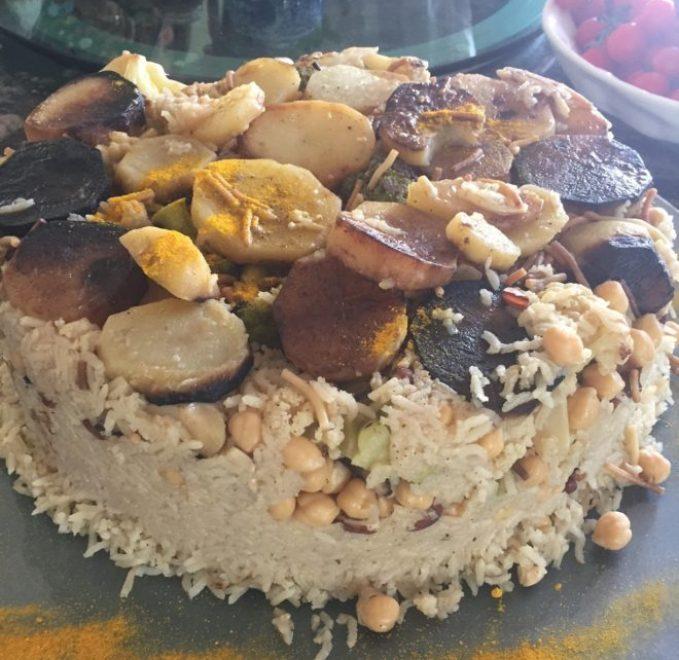 uma travessa com um bolo com várias camadas: na base arroz, intercalando com camadas de grão de bico e em cima batatas e cebolas fatiadas com pedaços de frango.