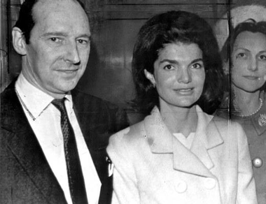 Lord Harlech ao lado de Jackie Kennedy - Ele veste terno escuro e ela veste um conjunto , cor clara. (a foto é preto e branco)
