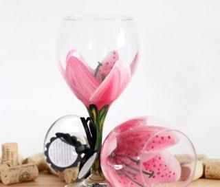 Taças de vinho em cristal, com desenhos de pétalas de flores e a haste na cor de folha. Uma está em pé e a outra tombada ao pé da outra. ao fundo muitas rolhas de garrafas de vinho.