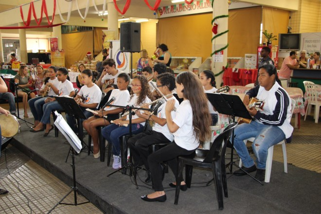 Várias crianças sentadas tocando diversos instrumentos.
