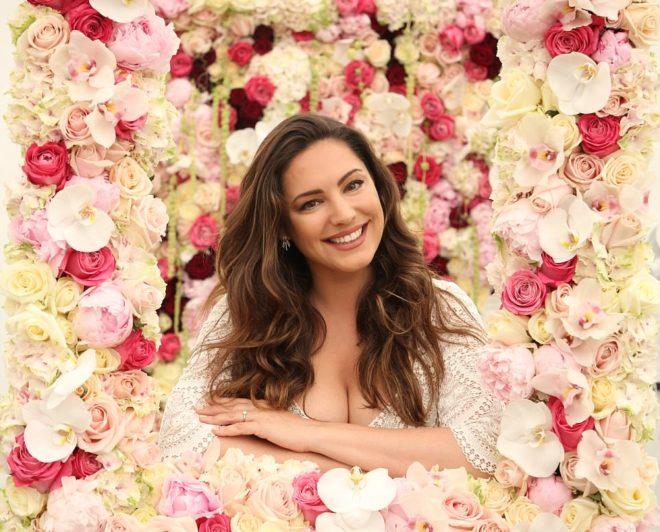 Durante a Chelsea Flowers Show, uma jovem está pousando numa janela totalmente revestida de flores de diversas cores, Ela tem cabelos longos, cor castanho escuro e sorri.