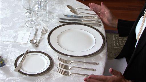 Mesa de refeição, com todos os utensílios, prato principal, prato de pãozinho, taças de vinho tinto, branco e água, com tres facas e duas colheres à direita e tres garfos a esquerda do prato, Sobre o pratinho de pão uma pequena faca. e acima do prato principal, uma colher pequena e um garfo pequeno, para comer a sobremesa.