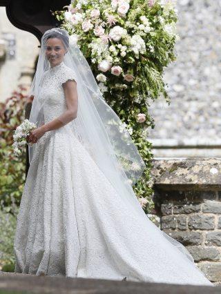 Pippa Middleton vestida de noiva parada junto a porta da igreja antes do seu casamento. Ela segura um pequeno buquê com flores brancas.