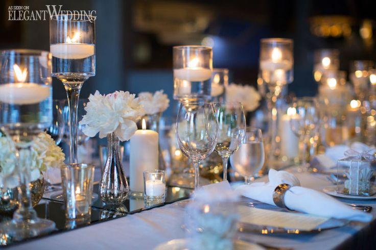 mesa de jantar, com todos os utensilios, em tons de prata, guardanapos brancos, e ao centro vários castiçais em vidro com pequenas velas acesas.
