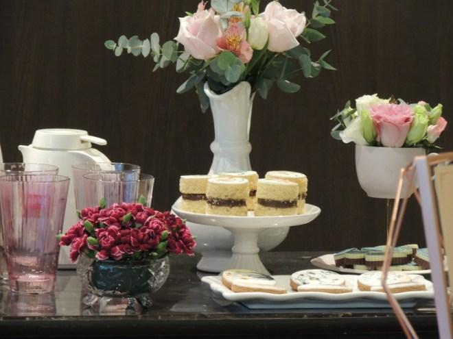 uma mesa de chá com os acessórios: um vasinho pequeno de flores vermelhas em primeiro plano. Logo atrás um prato alto com docinhos e ao seu lado uma bandeja de biscoitinhos pintados artisticamente com flores em sua superfície branca de açúcar glaciado. Ao fundo uma mini jarra branca com rosas com de chá.