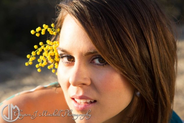 Beautiful woman with sprig of acacia flower