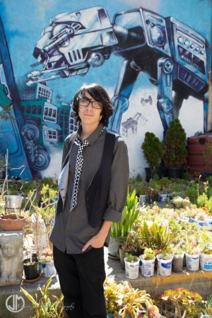 teen wearing a vest and tie in front of a mural in Oakland