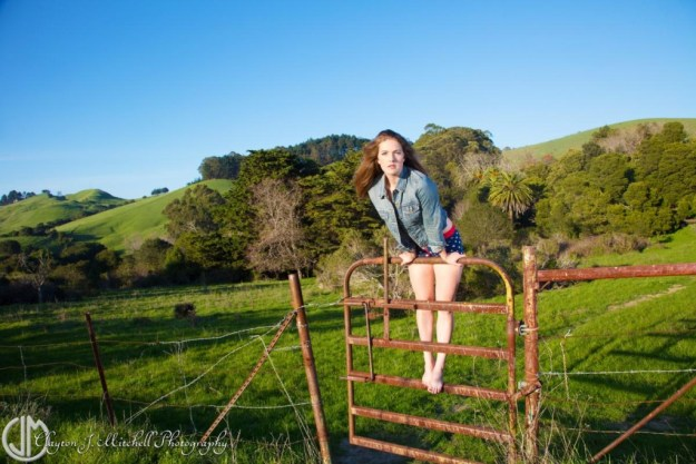beautiful woman climbing a fence