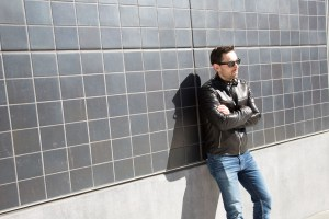 man in sunglass leans on black tile wall