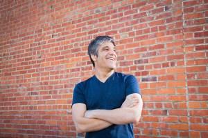 Lifestyle portrait of tech guru on brick wall