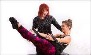 Pilates trainer assists client