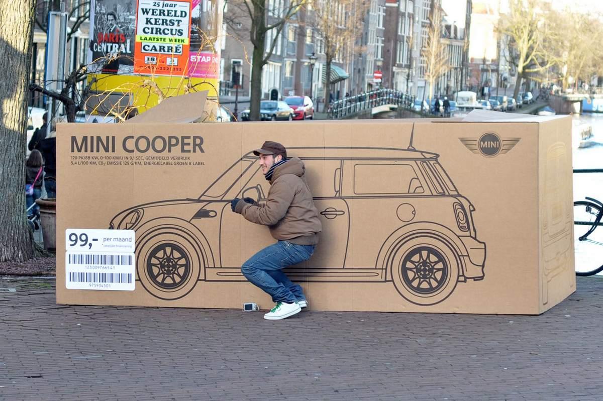 man met kartonnen doos van een mini