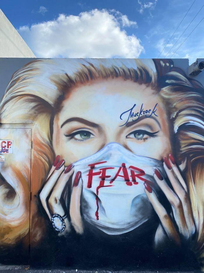Vrouw met mondkapje op buitenmuur: Angst